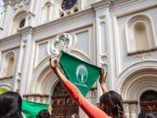 женщина в красной рубашке с длинным рукавом держит зеленый флаг